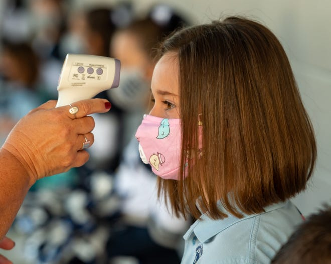 Students arrive for the first day of school at Carencro Catholic wearing facemask and checking their temperature. Thursday, Aug. 13, 2020.