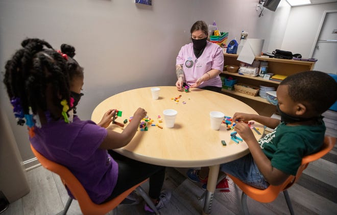 A school aide works with two children using Legos as a learning tool at Talk Childcare to Me, a daycare on Terry Road in Louisville, on Aug. 13.