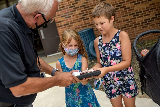 Lansing School District Superintendent Sam Sinicropi, left, gives an iPad to sisters Brooklyn, 5, left, and Aryanna Ostrander, 10, during a technology distribution event on Thursday, Aug. 13, 2020, at the Don Johnson Fieldhouse in Lansing. Remaining distribution dates are set for Aug. 14 and 17 for pre-K to third grade and Aug. 24-28 for grades 4-12. Distribution will be held at the Johnson Fieldhouse from 10 a.m. to 7 p.m.