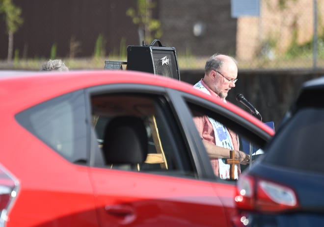 Rev. Gregory Bibler of the First Christian Church speaks to worshippers, sitting in their cars, Wednesday evening during the church's drive-in communion service. The services are at 6pm every 2nd and 4th Wednesday of the month during the pandemic.