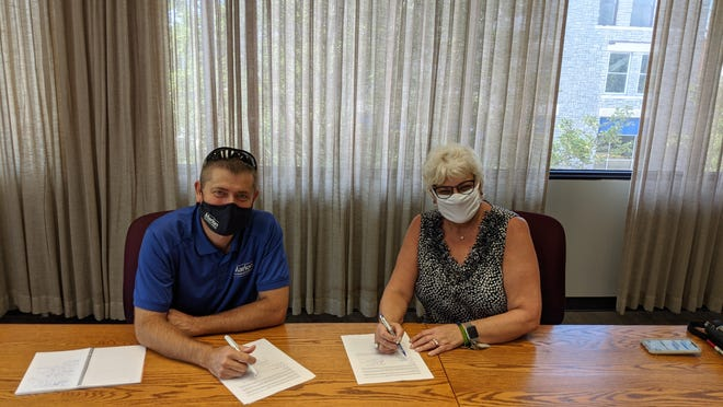 Marion Technical College President Ryan McCall signs a lease agreement with building owner Lois Fisher. MTC will open a 8,000 square foot satellite location next year at 107 N. Main Street in downtown Marion.