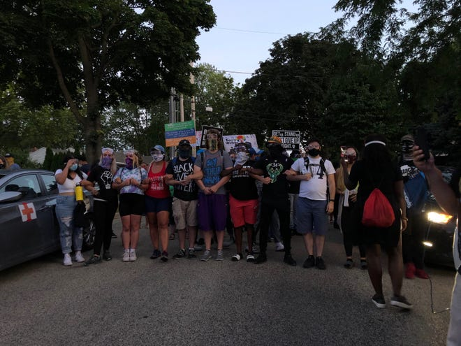 Protesters lock arms on Wednesday, Aug. 12, in Wauwatosa. A group was blocked off by police squad cars but they eventually made their way past the barricade.