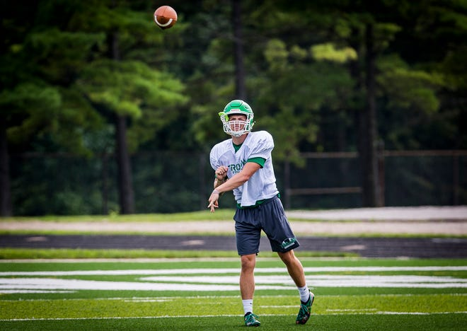 New Castle senior quarterback William Grieser tosses a pass during a football practice Aug. 13, 2020. The Trojans' season begins Saturday.