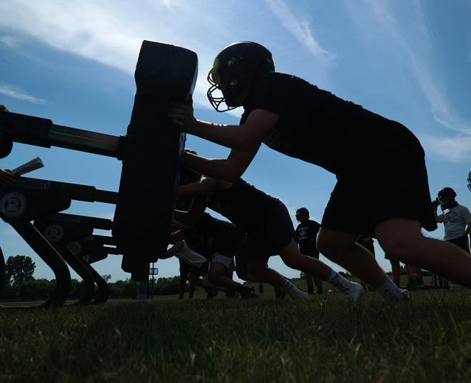 Plymouth Wildcat linemen hit the blocking sled during an Aug. 13, 2020 practice.