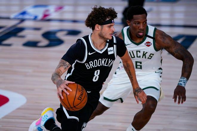 Milwaukee Bucks guard Eric Bledsoe (6) defends Brooklyn Nets guard Tyler Johnson (8) during the first half of an NBA basketball game Tuesday, Aug. 4, 2020 in Lake Buena Vista, Fla. (AP Photo/Ashley Landis).