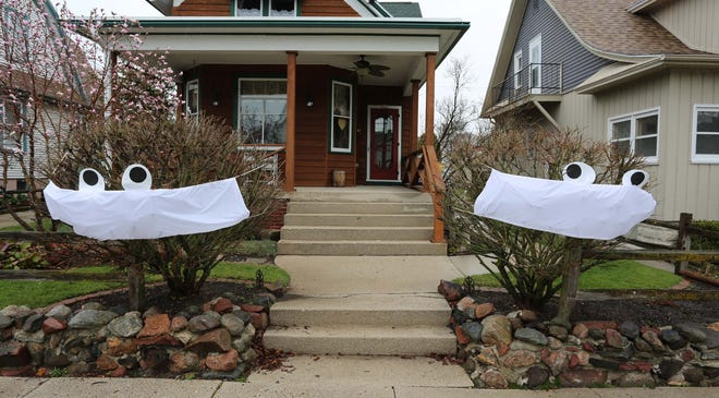 A pair of bushes are protected from COVID-19 virus with masks that the owner in the 300 block of Niagara gave them, Wednesday, April 29, 2020, in Sheboygan, Wis.