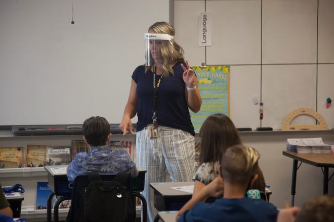 Mrs. Sparks, a teacher at Arrowhead Elementary, welcomes students and briefs them on mask use on the first day back in class for Washington County School District Thursday, Aug. 13, 2020.