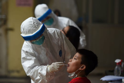 A health workers wearing protective clothing makes a swab test for COVID-19 coronavirus on residents at Hoan Kiem district medical centre in Hanoi on August 13, 2020.