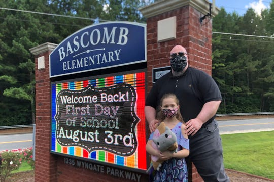 John Barrett and his daughter Autumn pose for photos outside Bascomb Elementary School in Woodstock, Ga., Thursday, July 23, 2020. Barrett says he will educate his daughter virtually and keep her out of in-person classes in Cherokee County schools, even though he's worried she will fall behind on her special education plans, because of concerns about COVID-19's spread.