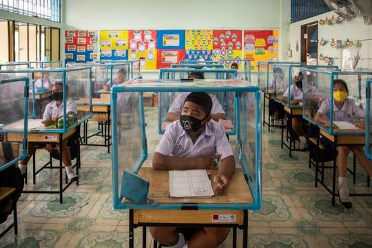 Los estudiantes tailandeses usan máscaras faciales y se sientan en escritorios con pantallas de plástico utilizadas para el distanciamiento social en la escuela Wat Khlong Toey el 10 de agosto de 2020 en Bangkok, Tailandia. A principios de julio, la escuela Wat Khlong Toey reabrió sus puertas a sus aproximadamente 250 estudiantes luego de la relajación de las medidas de cierre durante la pandemia de COVID-19.