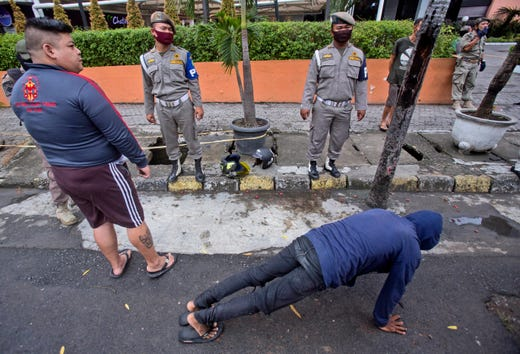 Public Order Agency officers watch as a man does push ups as a punishment for violating city regulation requiring people to wear face mask in public places as a precaution against the new coronavirus outbreak, in Medan, North Sumatra, Indonesia, Wednesday, Aug. 12, 2020.