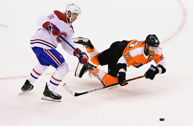 Flyers captain Claude Giroux falls to the ice as he battles Canadiens center Jesperi Kotkaniemi for the puck during Game 2 Friday. [Frank Gunn/AP]