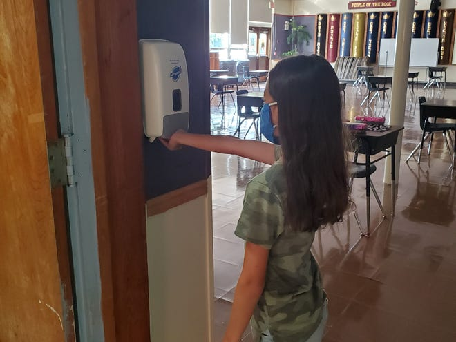 Molly Goldfarb, a student at Abrams Hebrew Academy in Yardley, checks out one of many hand sanitizing dispensers she will be using when school starts on Tuesday. [photo: COURTESY ABRAMS HEBREW ACADEMY]