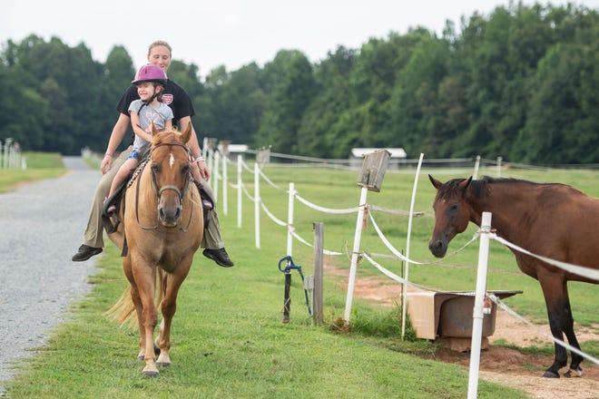Robin Lambert, 5, enjoys a trail ride accompanied by instructor Cassidy Garwood at Garwood Equestrian Center in Lexington in July.
