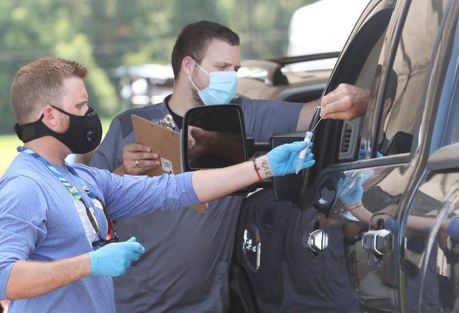 A client slips a swab back into the container held by a medical staff member, Friday August 14, 2020 at the Volusia County Fairgrounds coronavirus test site.  The new site opened Friday and is expected to run Thursdays through Tuesdays for the next four weeks.
