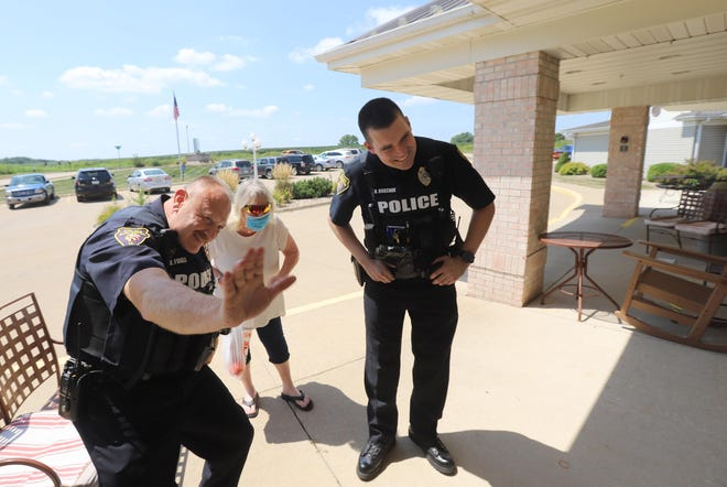 Burlington Police officers Rodney Fogle and Nate Hoschek and Marlene Jacobs wish Regina Olomon, inside, a happy birthday outside OakView Nursing and Rehabilitation Friday in Burlington. The officers were called into action by Regina's daughter Gina who lives in Louisiana. Jacobs is her sister from Burlington.