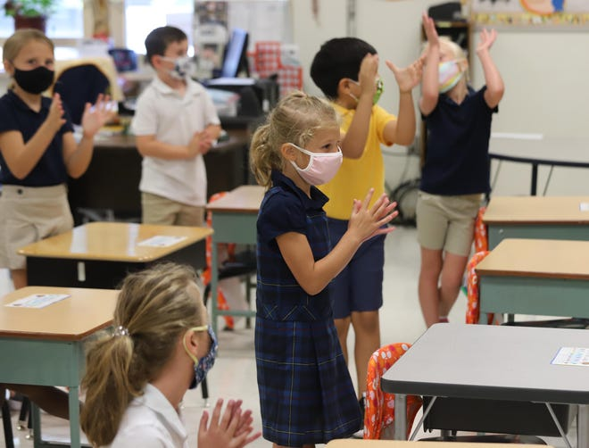 Notre Dame Elementary School first grade students practice a clapping rhythm pattern during music class August 11 in Burlington.