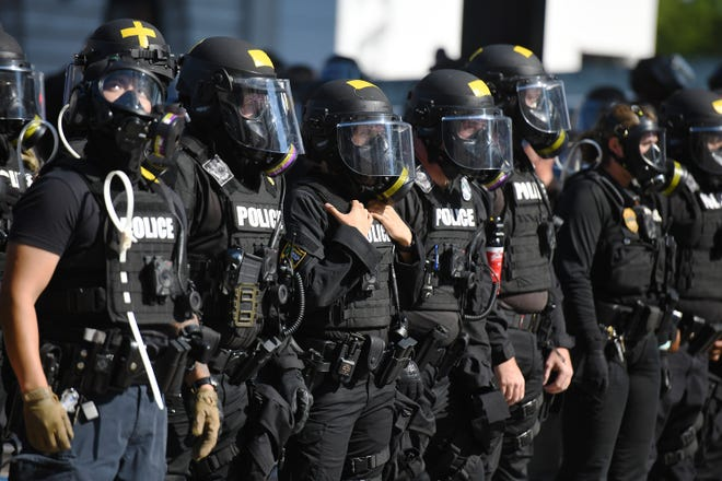 Jacksonville sheriff's officers in riot gear block off East Bay Street to shield protesters from the Main Street bridge on May 31. [Bob Self/Times-Union]