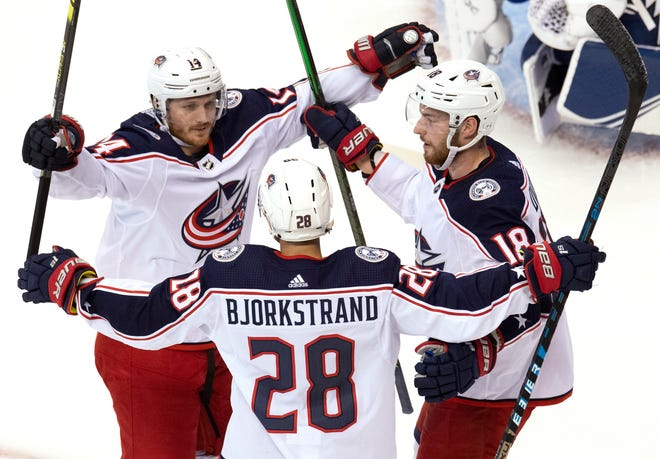 Columbus Blue Jackets right wing Oliver Bjorkstrand (28) is congratulated by teammates Gustav Nyquist (14) and Pierre-Luc Dubois (18) after scoring against the Tampa Bay Lightning on Thursday in Toronto. [FRANK GUNN/THE CANADIAN PRESS]