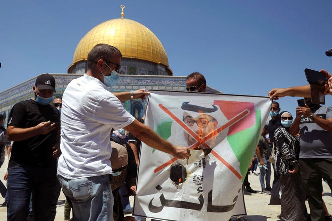 Palestinian protesters burn a banner showing Abu Dhabi Crown Prince Mohamed bin Zayed al-Nahyan during a protest against the United Arab Emirates' deal with Israel near the Dome of the Rock Mosque in the Al Aqsa Mosque compound in Jerusalem's old city, Friday, Aug. 14, 2020. (AP Photo/Mahmoud Illean)