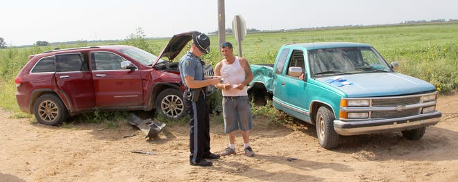 Kansas Highway Patrol Trooper Micah Polson gets information from 47-year-old John Kitts of Pratt after he was involved in a two-vehicle accident at NW 110th Street and NW 20th Avenue on Aug. 13.