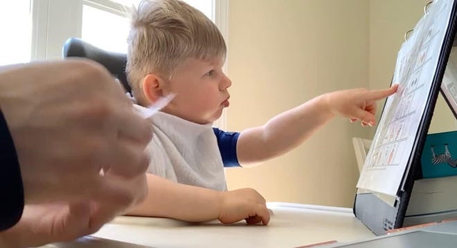 """Three-year-old Coby pushing the word 'Go' on a printed communication board for his mom April Berry to play """"Elmo's World"""" on YouTube in April of 2020."""