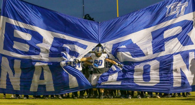 Bartram Trail co-captain Phillip Burnett breaks through the banner during an Oct. 18, 2019 football game against Oakleaf.