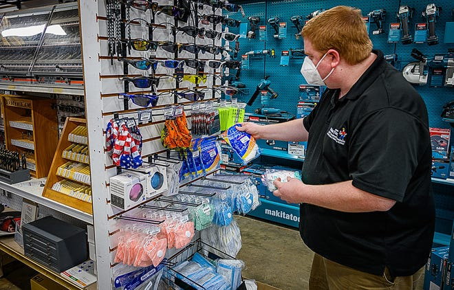 Ernie's Tool & Specialty Company manager Nathan Burres restocks face masks in his store in St. Augustine on Friday. [PETER WILLOTT/THE RECORD]