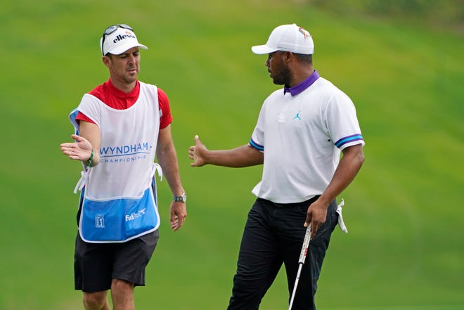 Harold Varner III, right, celebrates with his caddie after a par on the 18th hole to finish Thursday's first round of the Wyndham Championship at Sedgefield Country Club.