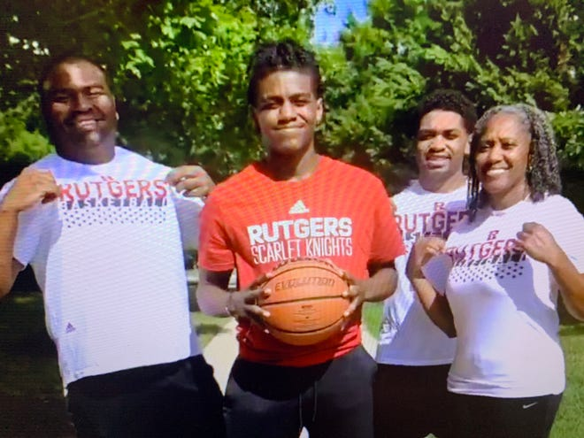 Jalen Miller, center, wears a Rutgers shirt during his commitment video