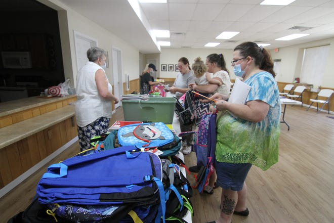 Parents stock up on school supplies at a giveaway inside Vision Baptist Church Aug. 12.