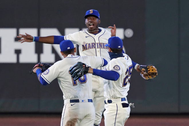 Seattle Mariners outfielders Kyle Lewis, center, Tim Lopes (10) and Dylan Moore (25) leap together in celebration after the team beat the Colorado Rockies in a baseball game on Aug. 9 in Seattle. (AP Photo/Elaine Thompson)