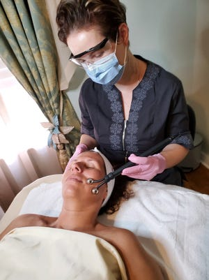 Corina Gata of Royal European Beauty Skin Care Studio  in Cocoa Village performs a microcurrent treatment on client Kim O'Grady as part of the salon's facial tissue stimulation therapy.
