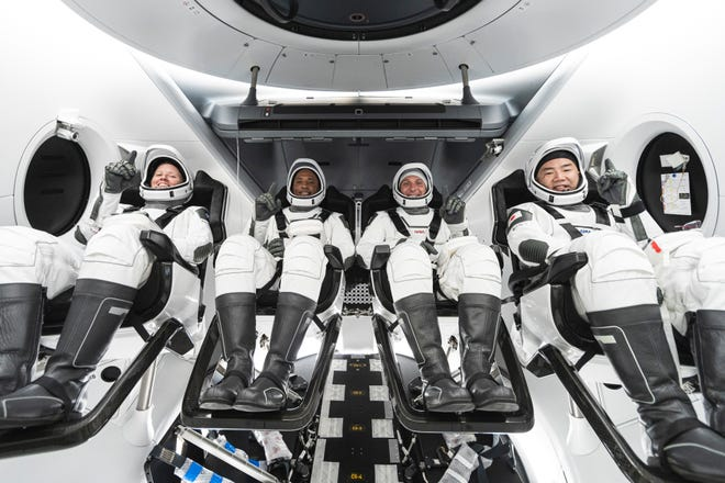 NASA's SpaceX Crew-1 crew members are seen seated in the company's Crew Dragon spacecraft during crew equipment interface training. From left to right are NASA astronauts Shannon Walker, mission specialist; Victor Glover, pilot; and Mike Hopkins, Crew Dragon commander; and JAXA astronaut Soichi Noguchi, mission specialist.