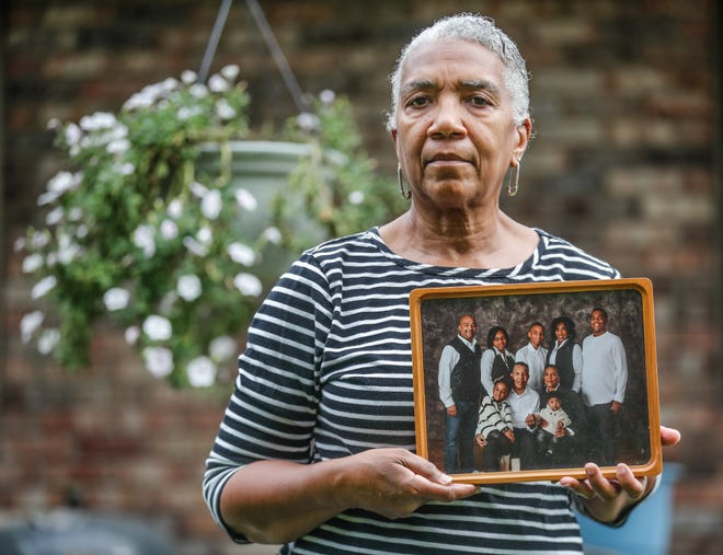 Hazel Nave, widow of Edward Nave, on  April 6, 2020, before he could be tested for COVID-19, at Bethany Pointe Health Campus, holds a family portrait outside her Anderson Ind. home, Friday, August 14, 2020. Bethany Pointe Health Campus was the site of one of the most significant outbreaks in an Indiana nursing home.