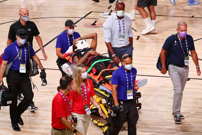 Aug 14, 2020; Lake Buena Vista, Florida, USA; Miami Heat forward Derrick Jones Jr. (5) covers his face with a towel while he is taken off the court by medical personnel after colliding with Indiana Pacers center Goga Bitadze (not pictured) during the second half of a NBA basketball game at AdventHealth Arena. Mandatory Credit: Kim Klement-USA TODAY Sports