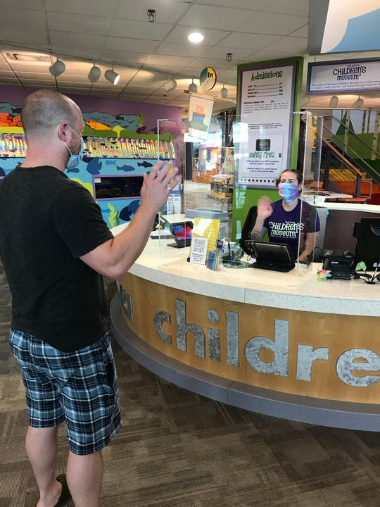 Staff at the Iowa Children's Museum wave at each other through a protective barrier at a safe social distance, in July 2020.