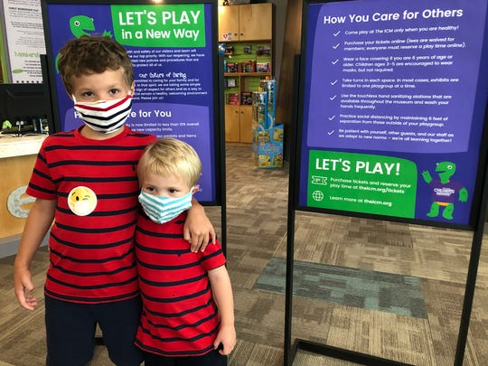 Two young guests visit the Iowa Children's Museum in July 2020 stand in front of a sign describing the facilities social distancing rules in light of COVID-19.