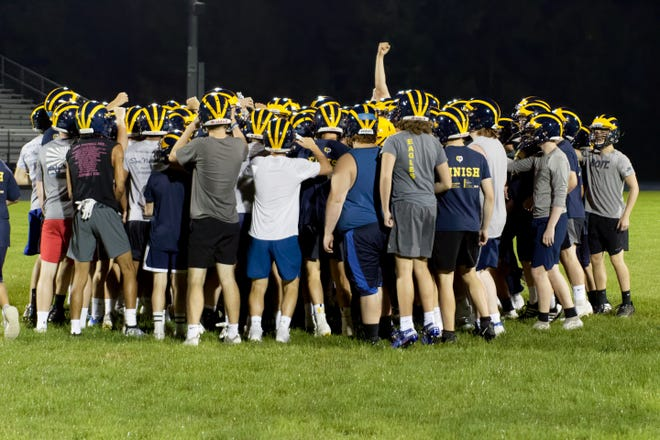 Hartland players gather during the opening day of high school football practice in 2019.