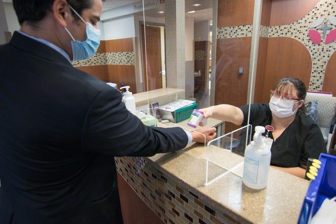 Amanda Hall checks the temperature of Bobby Maldonado of Saint Joseph Mercy Health System at St. Joseph Mercy Livingston Hospital, Thursday, Aug. 13, 2020. The hospital is conducting a community survey on health and social needs.