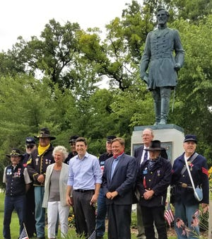 U.S. Rep Bryan Steil (center in blue short) stands with Sons of Union Veterans of the Civil War members and local officials in Wind Lake on Aug. 3 beneath the statue of Col. Hans Christian Heg. While promoting his efforts to rename the Muskego Post Office in honor of Heg, Steil visited the Wind Lake statue, which will be used to help restore an identical statue at the State Capitol damaged during protests in Madison.
