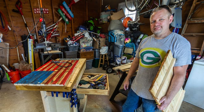 Woodworker Curt Klein of Milwaukee uses a variety of tools, clamps and home built jigs to create handcrafted wooden flags in his home workshop as seen on Friday, August 14, 2020. What began as a hobby has turned into a part-time job after his wife posted his work on facebook.