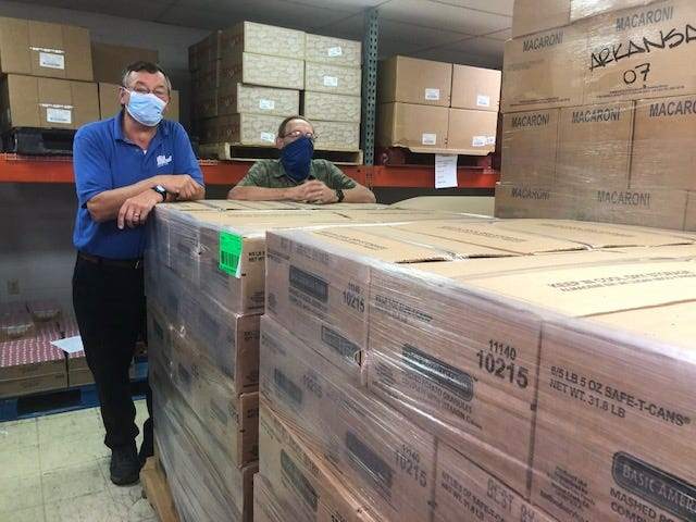 The Food Bank of North Central Arkansas recently accepted 39,000 pounds of food from The Church of Jesus Christ of Latter-Day Saints in Mountain Home. Shown above (from left) church member Eric Chase and Food Bank Chief Operating Officer Tim Riggs.