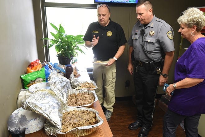 Sgt. Scott Thrasher, left, deputy Clay Maple, center, and administrative secretary Gayla Tate look over food brought to the Baxter County Sheriff's Office on Friday. The man who brought the food, a member of St. Peter's Catholic Church, said he wished to thank law enforcement and remain anonymous. He was the second person to bring food to the BCSO in a three-day span.