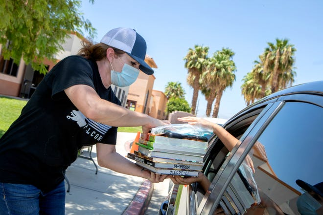Bobby Duke Middle School Principal Michele DeJournett hands out textbooks and iPads to students during a drive-up distribution at the school in Coachella, Calif., on Tuesday, August 11, 2020. Coachella Valley Unified School District begins online instruction on Aug. 14.