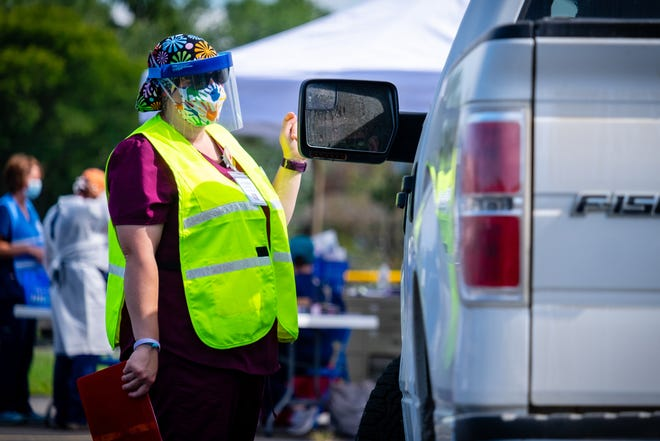St. Clair County Health Department Public Health Technician Liz Foley talks to a patient at a clinic held by the health department Thursday, Aug. 13, 2020, at Yale High School. The health department paused its drive-thru services to transition to sites at area schools.