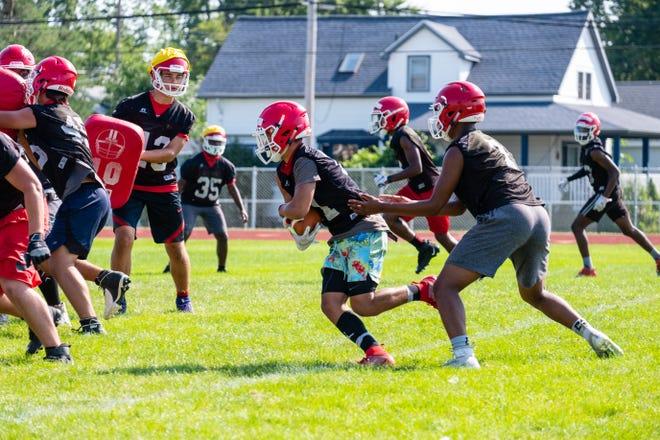 Port Huron High School football players run during practice Friday, Aug. 14, 2020, at Port Huron High School.