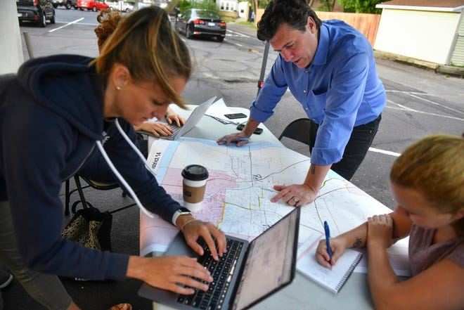 Aric Putnam looks at a map of Senate District 14 while working with campaign staff members Wednesday, Aug. 12, 2020, in St. Cloud.
