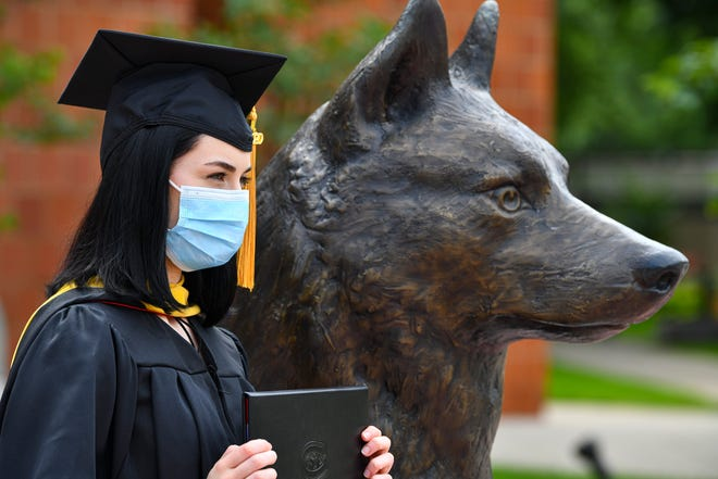 Rachelle Vadnais poses with her master's degree in social work next to the school mascot in Husky Plaza following St. Cloud State University spring semester commencement ceremonies Friday, Aug. 14, 2020, in St. Cloud.
