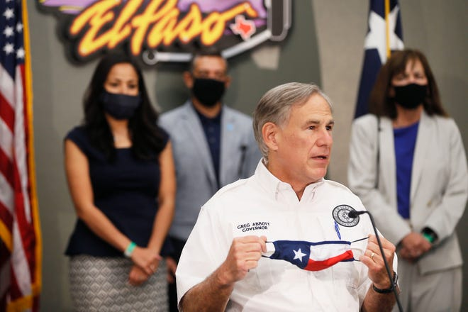 Texas Gov. Greg Abbott puts his mask back on during a meeting with local officials providing an update on COVID-19 in El Paso Thursday, Aug. 13, at the El Paso Regional Communications Center.